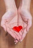 一红色心脏在女性手上 免版税库存图片
