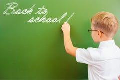 一级男小学生在有白垩的黑板写了在教室 免版税库存图片