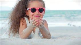 一美丽的女孩,逗人喜爱微笑的特写镜头画象桃红色玻璃的看照相机,说谎在沙子  影视素材