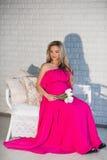 一美丽的孕妇明亮的礼服和长的hai的画象 库存照片