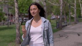 一美丽的少女步行沿着向下街道并且吃冰淇淋在一个热的夏日,当有心情时 股票录像