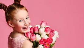 一美丽的少女的画象拿着虹膜和郁金香的大花束礼服的在桃红色背景 免版税库存图片