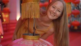 一美丽的年轻女人的慢动作射击看从一个红色灯笼的后面和笑 庆祝的概念 股票视频