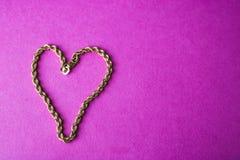 一美丽的金黄欢乐链子独特编织的纹理以在桃红色紫色背景和拷贝空间的心脏的形式 库存照片