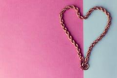 一美丽的金黄欢乐链子独特编织的纹理以在桃红色紫色蓝色背景和拷贝空间的心脏的形式 库存照片