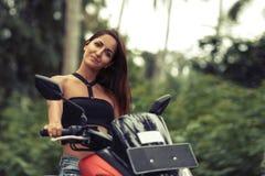 一美女的画象一辆摩托车的在自然绿色背景 库存图片
