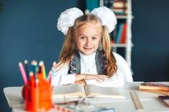 一美女的画象在教室 有坐在桌和学习上的白色弓的小女小学生 教育和 库存图片