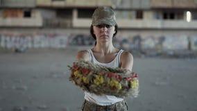 一美女的画象拿着花圈的伪装盖帽和白色T恤的看照相机 战士妇女 影视素材