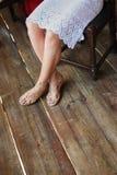一美女的腿一件白色礼服的,坐一把椅子和鞋子在白色凉鞋,木地板 库存照片