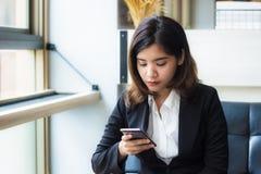 一美好亚洲女商人行政放松在咖啡店藏品和使用应用在她巧妙的电话 免版税库存图片