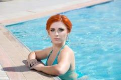 一美好妇女离开的画象游泳池 美丽的长的头发由蓝色水池水晒黑了式样摆在 库存照片