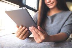 一美好的亚洲妇女` s递拿着和使用片剂个人计算机 免版税库存照片