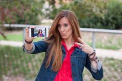 一美好的少妇selfie的画象在有sm的公园 免版税图库摄影