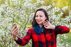 一美好的年轻女人selfie的画象在有智能手机做的公园 库存照片