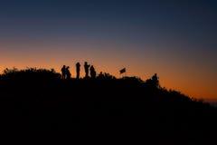 一群人在站立山在日出 库存图片