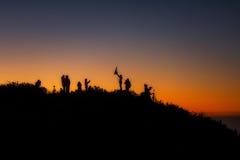 一群人在站立山在日出 免版税库存照片