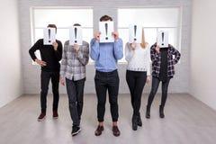 一群人站立与箭头并且用与惊叹号的板料包括他们的面孔 库存照片