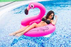 一群桃红色火鸟的女孩在太阳镜的水池 夏天职业 免版税库存照片