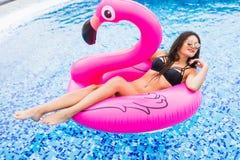 一群桃红色火鸟的女孩在太阳镜的水池 夏天职业 库存图片