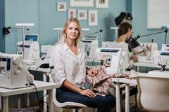 一聪明俏丽的白肤金发的妇女佩带的白色衬衫缝合与电缝合机器 时尚,裁缝的 免版税库存照片