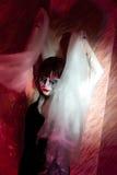 一股烟的吸血鬼女孩在红色 免版税库存照片