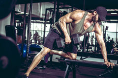 一胳膊在健身房的哑铃行 免版税库存图片