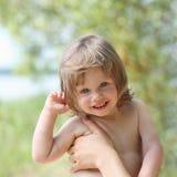 一自然本底走的愉快的矮小的微笑的孩子 库存照片