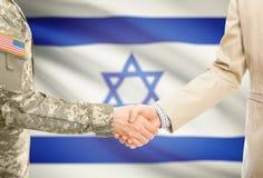 一致和民用人的美国军人衣服的与在背景-以色列的充分国旗握手 免版税库存照片