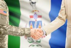 一致和民用人的美国军人衣服的与在背景-育空的某一加拿大省旗子握手 库存照片