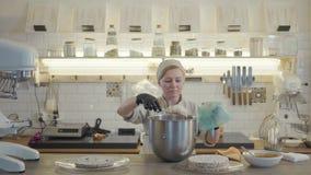 一致和黑手套的妇女在有许多厨房用具的现代厨房里站立并且投入了白色奶油 股票录像