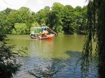 一艘两层河船即刻地清扫在含水表面反对绿色公园区域的背景 免版税库存图片