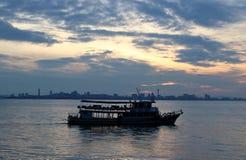 一艘乘客渡轮的剪影在日出期间的 库存照片