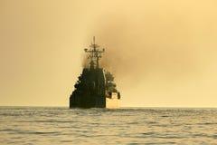 一艘军舰的剪影海上的 库存照片