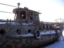 一艘凹下去的船的老生锈的船身在岸的 免版税库存图片