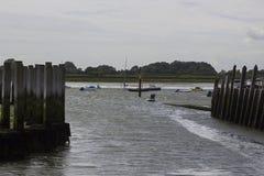 一艘可膨胀的充气救生艇的一个人荡桨反对往滑动式造船架的强风在Bosham港口在西萨塞克斯郡 免版税库存图片
