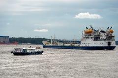 一艘大驳船和一条小船在河 免版税库存图片