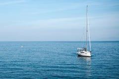 一艘小帆船停泊了在离海岸的附近,在背景海 免版税图库摄影