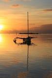 一艘帆船的剪影在日落的海上 库存图片