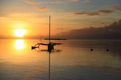 一艘帆船的剪影在日落的海上 图库摄影
