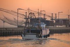 一艘捕鱼船移动朝海在日出,意大利 免版税库存图片