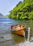 一艘桔黄色划艇阻塞在湖的边缘 免版税库存图片
