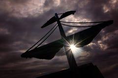 一艘海盗船的帆柱在日落的 图库摄影