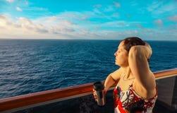 一艘游轮的阳台的妇女在日出的 图库摄影
