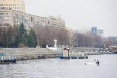 一艘白色皮船的一个人在城市riverbank01附近 免版税库存照片