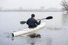 一艘白色皮船的一个人在城市riverbank04附近 免版税库存照片