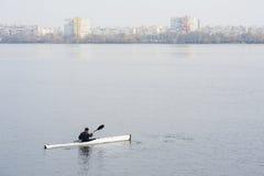 一艘白色皮船的一个人在城市riverbank03附近 库存照片