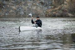 一艘白色皮船的一个人在城市riverbank05附近 图库摄影