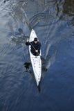 一艘白色皮船的一个人在城市riverbank07附近 库存照片