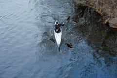 一艘白色皮船的一个人在城市riverbank06附近 免版税库存图片