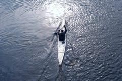 一艘白色皮船的一个人在城市riverbank08附近 免版税库存图片